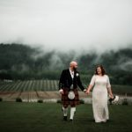 Bride and groom walking in the foggy vineyard after their wedding ceremony at Abbey Road Farm Wedding venue in Carlton Oregon.