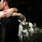 bride and groom embracing and kissing while holding a wedding bouquet overlooking the lake at Hornings Hideout wedding venue in North Plains Oregon by Oregon Wedding Photographer Dionne Kraus